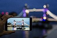 UK, London, man's hand holding smartphone with photo of Tower Bridge at twilight - MAUF000079