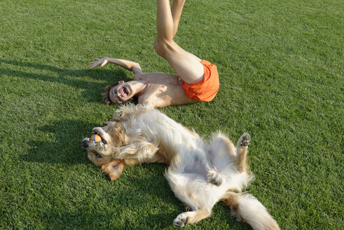 Teenage boy playing with Golden Retriever on lawn - LBF001288