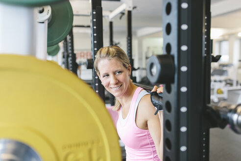 Smiling woman doing barbell squats in a power rack - MADF000707