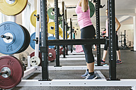 Woman lifting barbell in a power rack - MADF000710