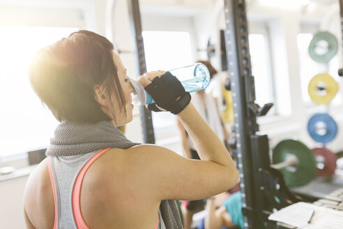 Woman drinking water in gym - MADF000749