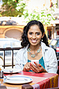 Portrait of smiling woman with smartphone sitting at table of an outdoor outdoor gastronomy - ABAF001950