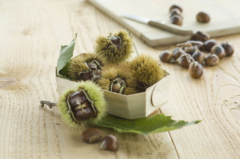Box with sweet chestnuts on wood - ASF005777