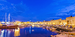 Greece, Rhodes, harbor, city wall and fishing boats at dusk - WDF003400