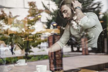 Man using digital tablet behind windowpane - ZEDF000001