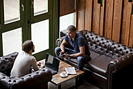 Two men with laptop sitting on couch in a lounge - ZEDF000004