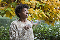 Young woman enjoying cup of coffee outdoors in autumn - MAUF000105