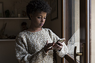 Young woman at the window looking at smartphone - MAUF000111