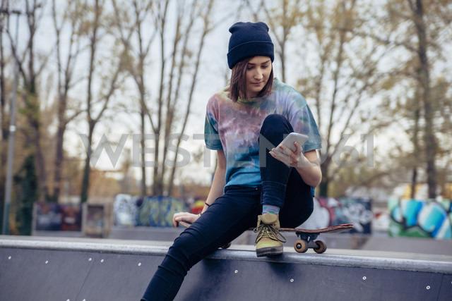 Young woman at skatepark looking at cell phone - ZEDF000015 - Zeljko Dangubic/Westend61