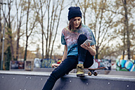 Young woman at skatepark looking at cell phone - ZEDF000015