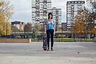 Portrait of young woman with skateboard - ZEDF000018