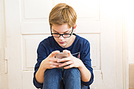 Boy looking at his smartphone - LVF004201