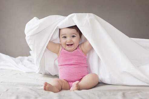 Smiling baby girl playing peek-a-boo under bed sheet - LITF000006