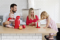 Family of four in the kitchen preparing apple sauce together - LITF000015