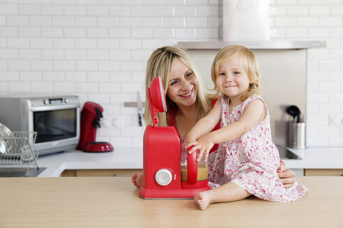 Mother and smiling daughter in the kitchen with kitchen machine - LITF000018