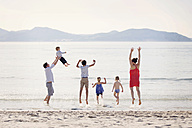 France, La Ciotat, couple with four children jumping in the air at seafront - LITF000039