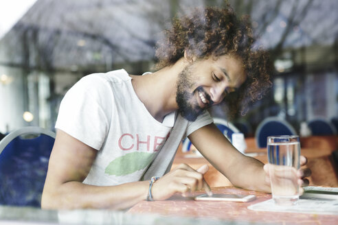 Portrait of smiling man sitting in a cafe using smartphone - GDF000908