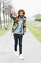 Portrait of happy man with dyed ringlets wearing camouflage jacket - GDF000914