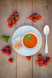 Bowl of tomato cream soup garnished with basil leaves and a recyclable wooden spoon - LVF004218