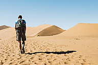 Namibia, Namib Desert, man with backpack walking  through the dunes - GEMF000506