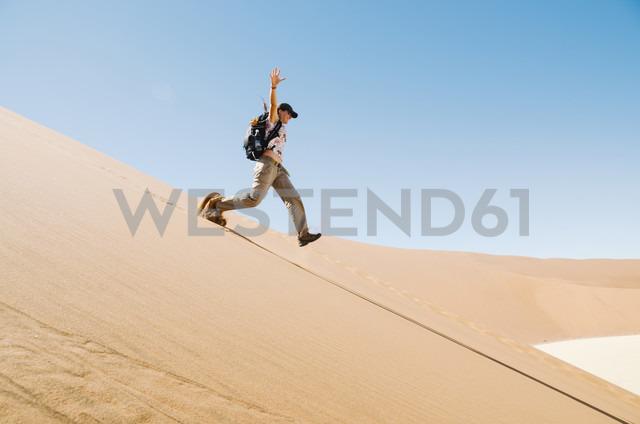 Namibia, Namib Desert, woman running down a dune - GEMF000509