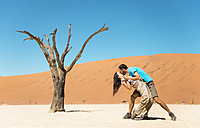 Namibia, Namib Desert, happy couple kissing next to dead tree in Deadvlei - GEMF000518