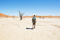 Namibia, Namib Desert, man with backpack walking through Deadvlei - GEMF000524