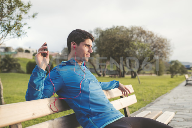 Athlete sitting on bench after training listening to music from smartphone - RAEF000688