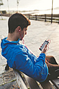 Athlete sitting on bench after training listening to music from smartphone - RAEF000691