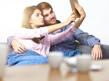 Young couple on couch taking selfie with digital tablet - DISF002265