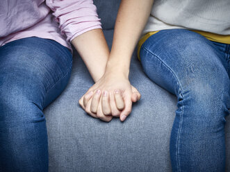 Partial view of lesbian couple holding hands on couch - DISF002271