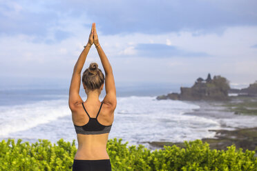 Indonesia, Bali, Tanah Lot, woman practising yoga at the coast - KNTF000187