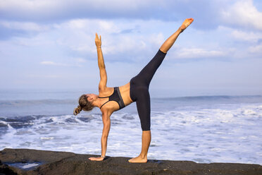 Indonesia, Bali, woman practising yoga at the coast - KNTF000190