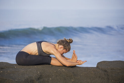 Indonesia, Bali, woman practising yoga at the coast - KNTF000193