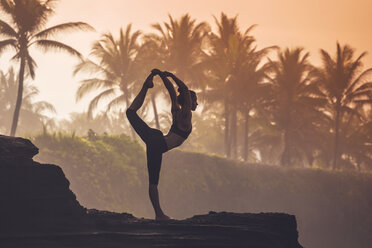 Indonesia, Bali, woman practising yoga at the coast at twilight - KNTF000196