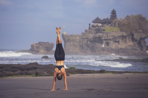 Indonesia, Bali, Tanah Lot, woman doing a handstand on the beach - KNTF000199