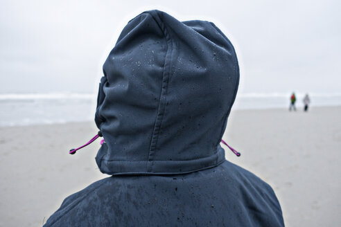Germany, Langeoog Island, person with wet hood on the beach - JATF000790