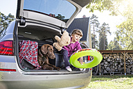 Girl in car boot with dog and teddy bear - FKF001616