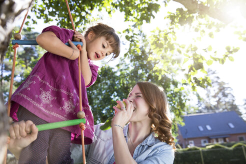 Mother eating an apple with daughter on rope ladder in garden - FKF001628
