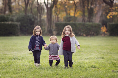 France, Provence, Marseille, Parc de Maison Blanche, three toddler girls holding hands in a field - LITF000059