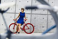 Woman with red racing cycle in front of concrete wall - GIOF000550