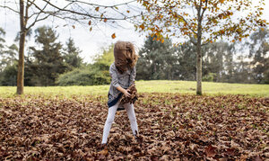 Little girl playing with autumn leaves on a meadow - MGOF001113