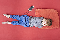 Little boy lying on bed hearing music with smartphone and earphones - MMFF001270