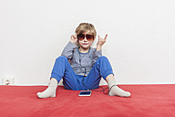 Little boy with sunglasses sitting on bed hearing music with smartphone and earphones - MMFF001276