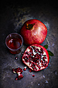 Sliced and whole pomegranate and glass of pomegranate juice on dark ground - KSWF001686