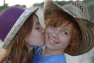 Girl kissing her smiling brother - LBF001298