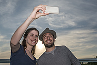 Smiling young couple taking a selfie with smartphone - PAF001499