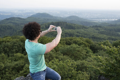 Germany, Siebengebirge, man taking a picture of view with smartphone on Mount Olivet - PAF001502