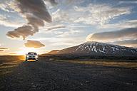 Iceland, car on gravel road under midnight sun - PAF001508