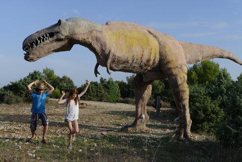 Croatia, Cape Kamenjak, boy and girl having fun at dinosaur educational trail - LB001301